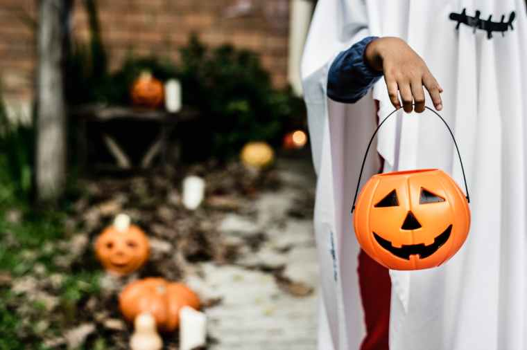 person carrying pumpkin bucket