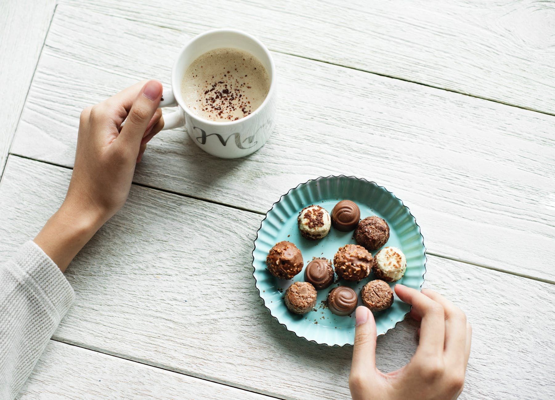 person holding chocolates and white ceramic mug