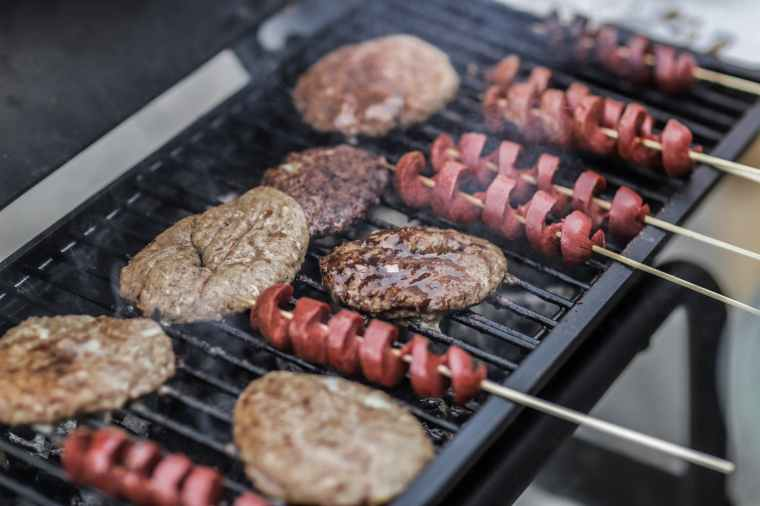 steaks and skewered sausages on grill