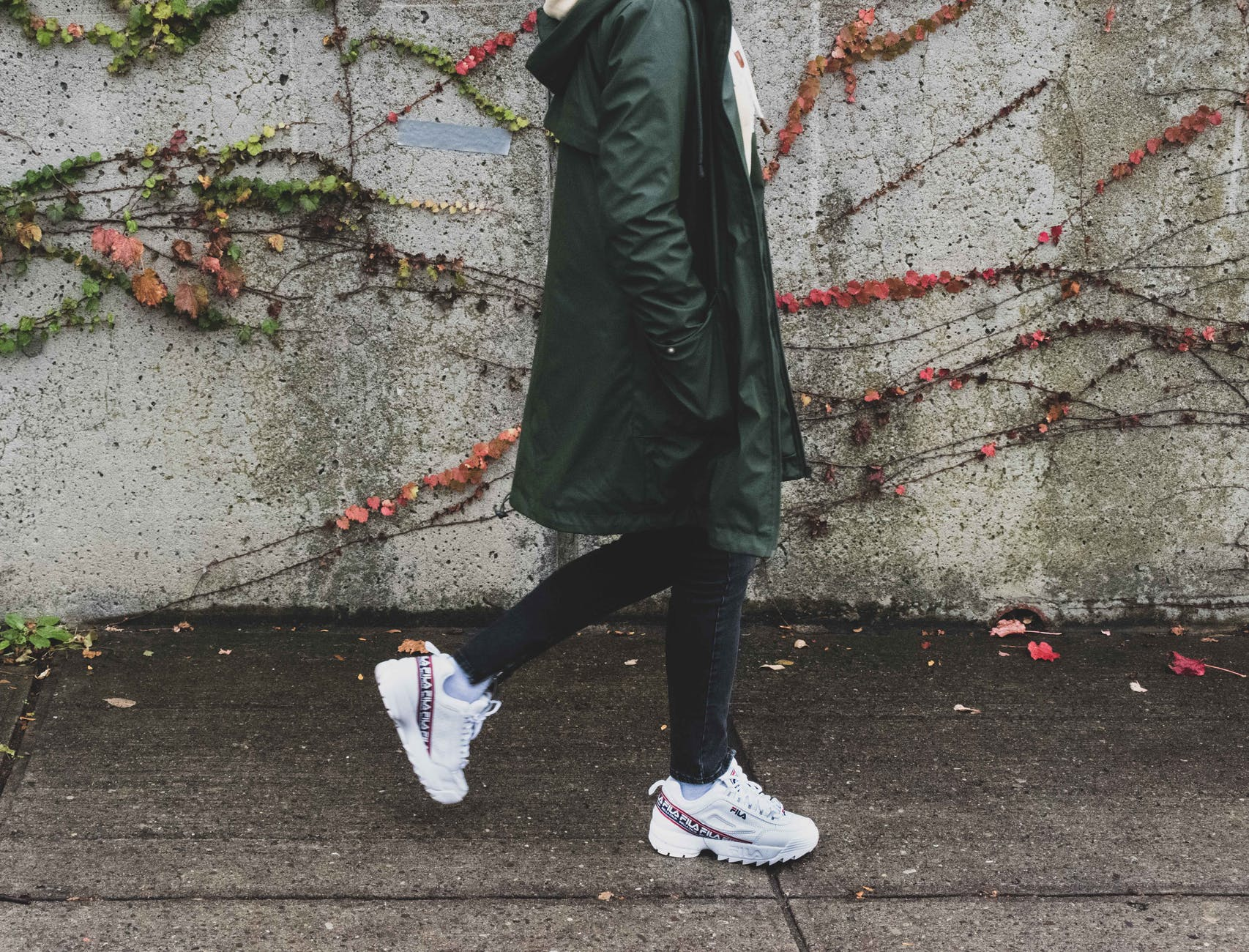 person wearing green coat and rubber shoes