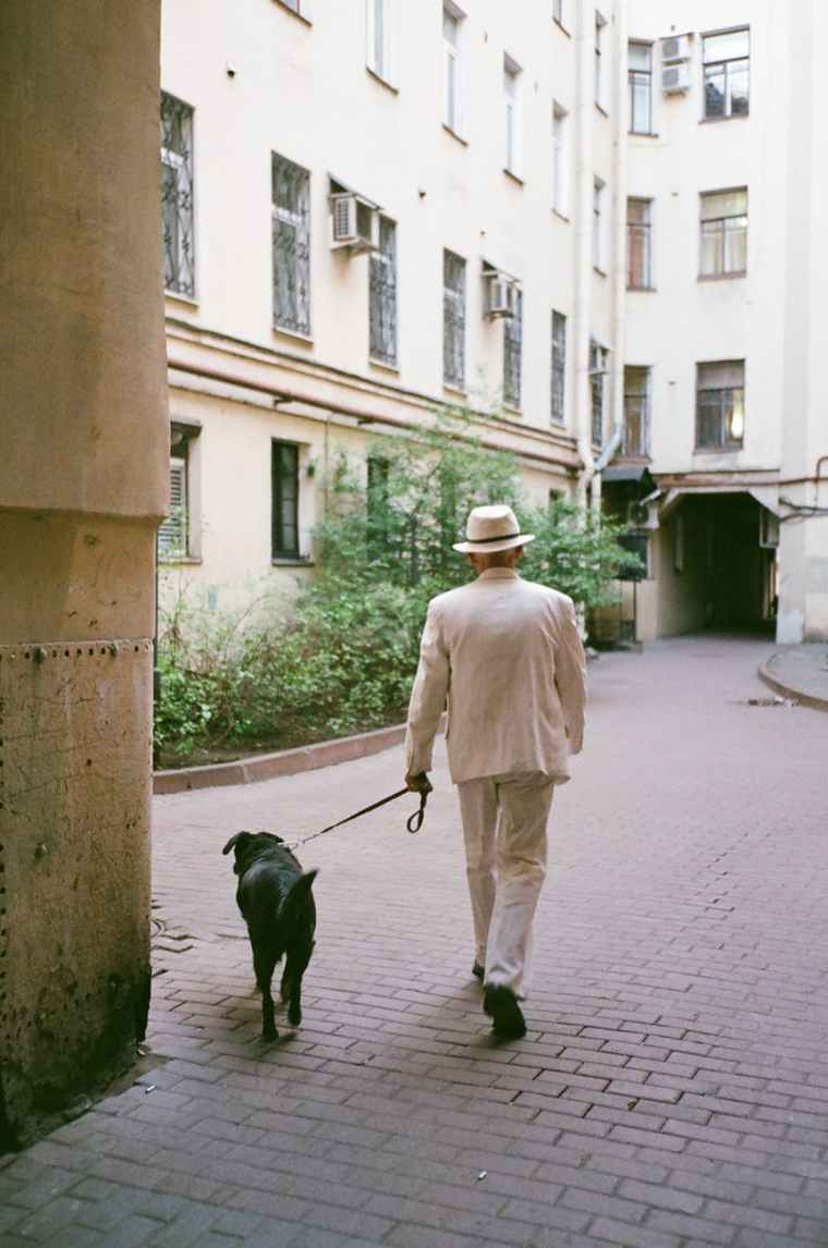 man wearing white suit walking with a dog